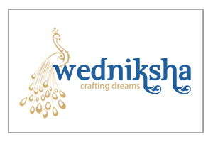 Beautifully Drawn Peacock In Golden Brown Followed By The Company Name In Dark Blue And Tag Line 'Crafting Dreams' Written In Golden Color.